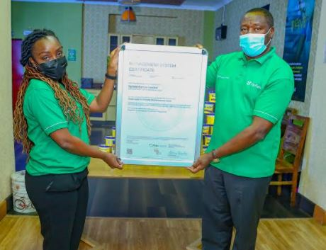 Upfield Kenya head of Regulatory affairs and Nutrition Phylis Obote hands over the FSCC certificate to Managing Director Upfield Eastern and Southern Africa peter Muchiri during a celebration of the awarding of the certification at Upfield Nairobi Offices