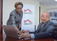 Equity Bank Kenya Managing Director, Gerald Warui (left) looks through the newly revamped American Express (AMEX) Membership Rewards website with Equity Bank Relationship Manager – Card Business, Susan Muigai (right).